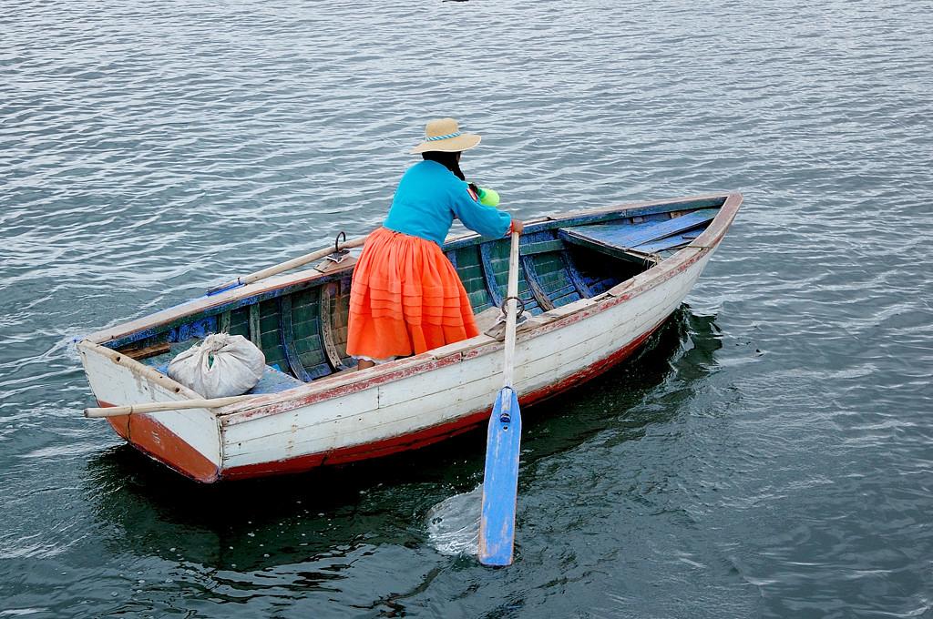 Девушка ловко управляется с веслами, причем гребет стоя