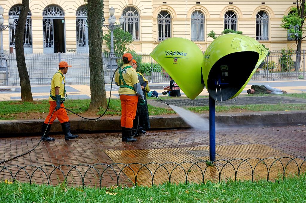Рабочие отмывают тротуары от бомжей. Обратите внимание на чела справа на заднем плане
