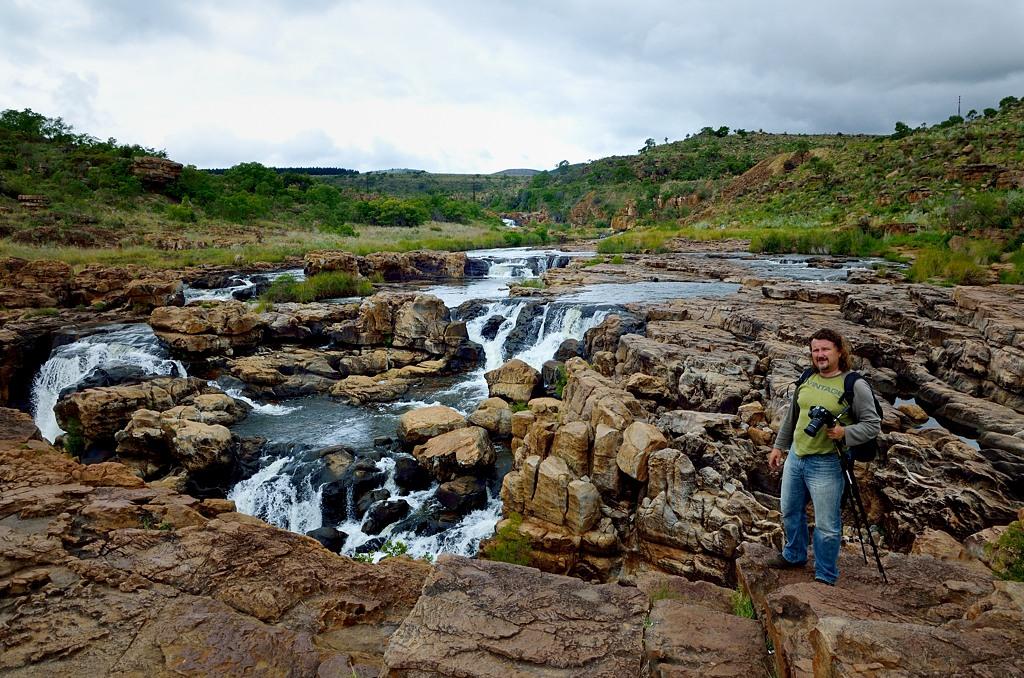 Мужик с треногой фотографирует водопад