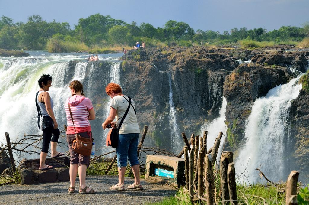 Народ фотографируется на фоне замбийской стороны водопада