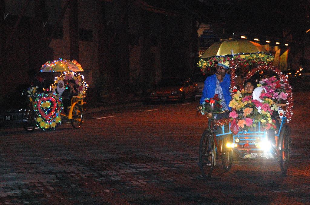 Велорикши рассекают ночью по центру Малакки как привидения