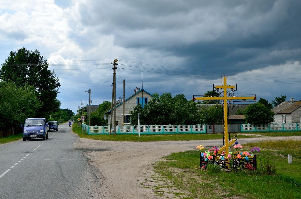 У въезда в каждую деревню стоит крест с цветами. Это означает, что деревня освящена.