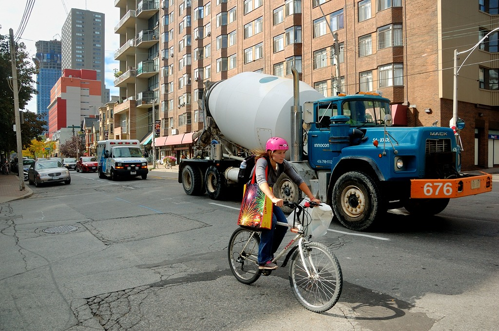 Велосипедистка в шлеме на фоне бетономешалки