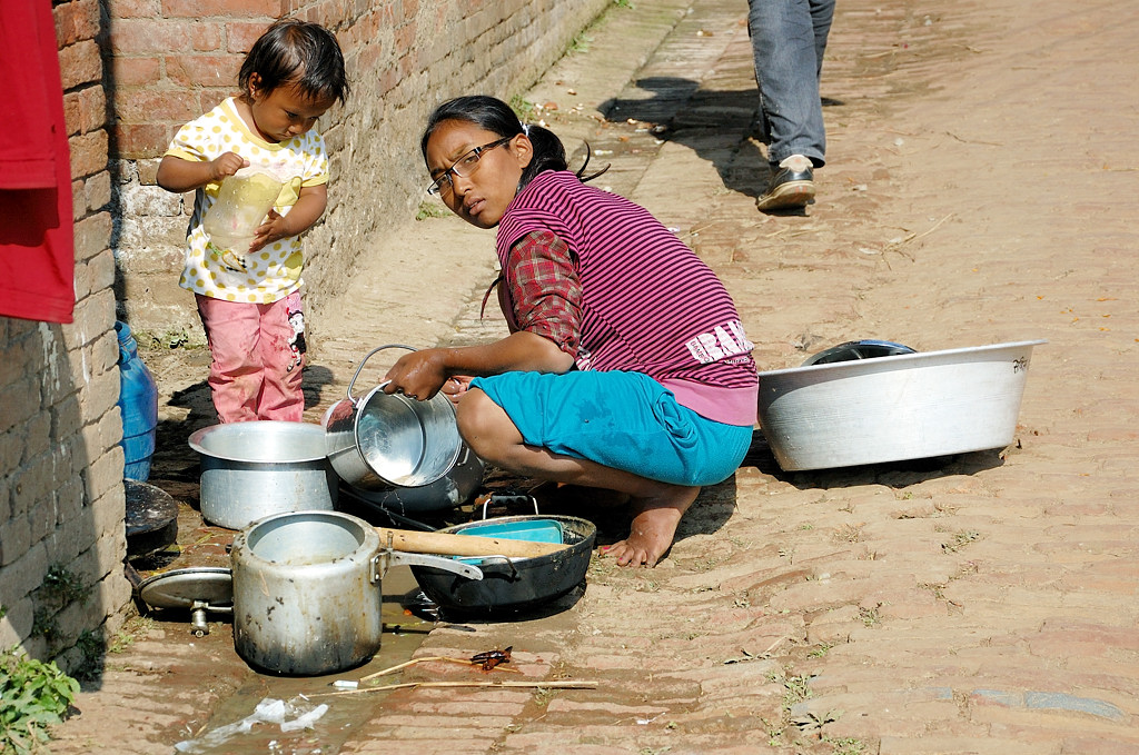 Местная жительница с ребенком и кастрюлями