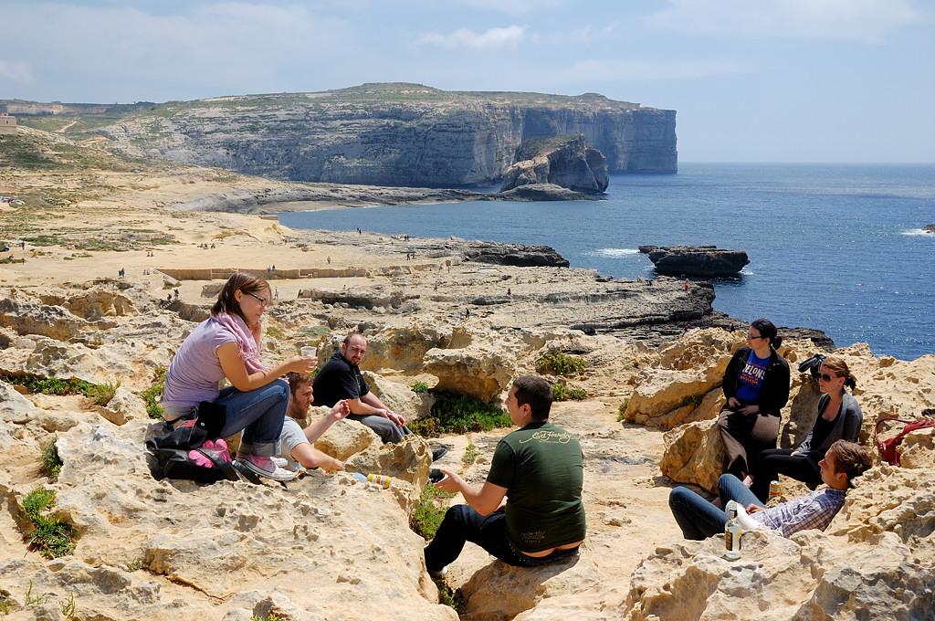Туристы сидят на скале над Лазурным Окном