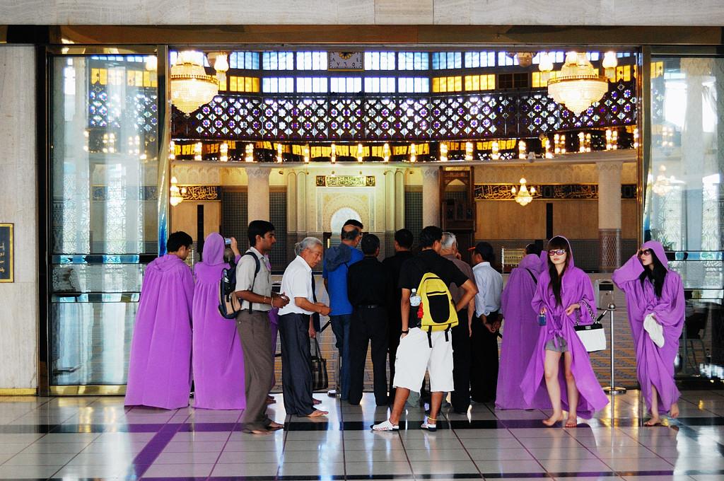 У входа в главный молельный зал. В сиреневых накидках - это не мусульманки, их специально выдают, чтобы