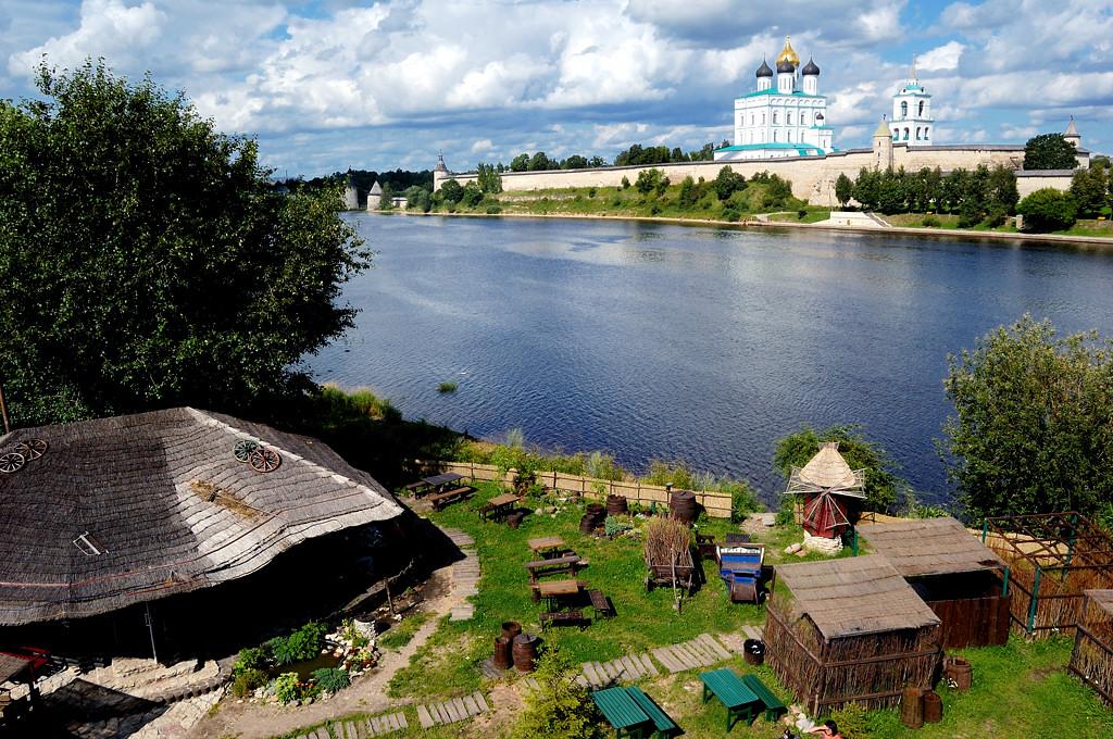Вид с Ольгинского моста на реку Великую и Кремль. На переднем плане ресторан в народном стиле
